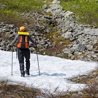 A girl with a backpack and trekking sticks is standing on a mountain glacier.