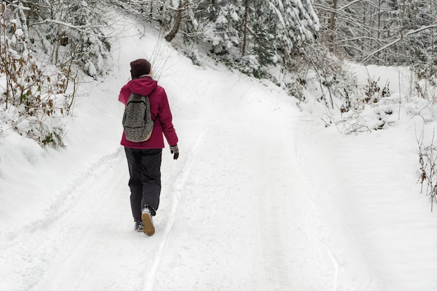 Girl with a backpack walking along the road in a snowy forest.