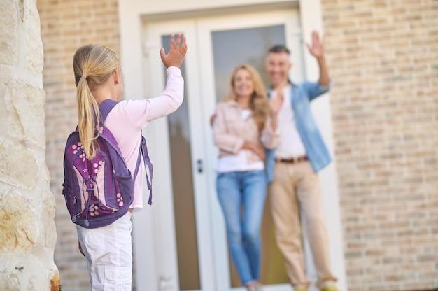 両親に別れを振るバックパックを持つ少女