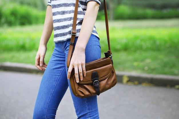 屋外で彼の肩にバッグを持つ少女