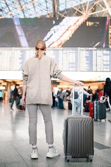 Девушка с багажом ждет вылета.