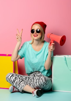 Girl with bags and megaphone near pink wall