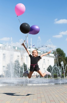 Girl with balloons at fountain