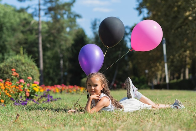 Girl with balloons lying in grass