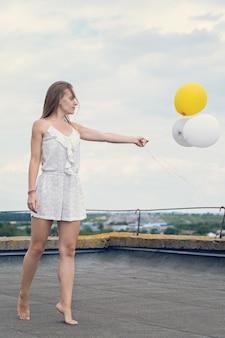 Девушка с воздушными шарами на крыше дома