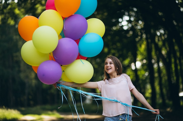 Girl with balloons in park
