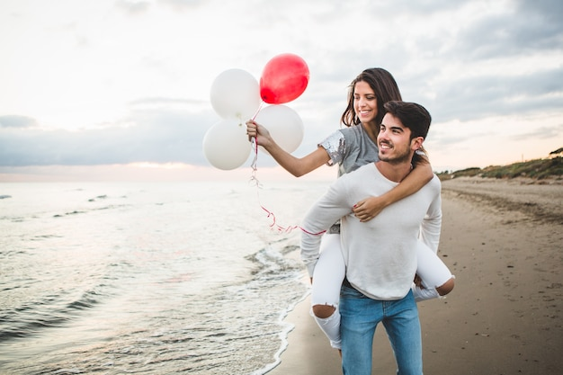 Girl with balloons while her boyfriend carries her on her back