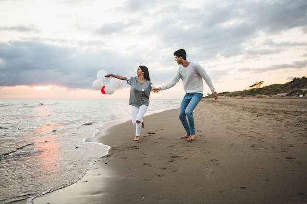 Girl with balloons while her boyfriend holds her hand
