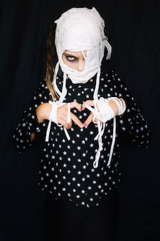 Girl with bandaged face making heart sign