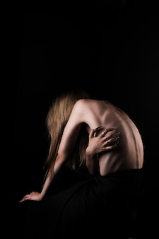 A girl with a bare back, severe thinness and protruding ribs