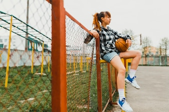 Girl with basketball in urban environment