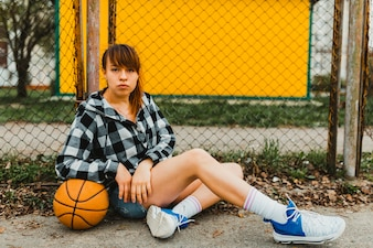 Girl with basketball sitting in front of fence