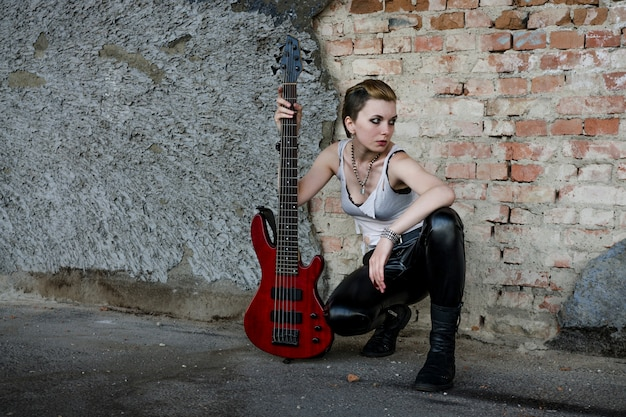 Girl with bass guitar at abadoned place