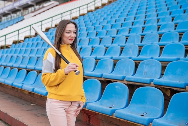 Girl with a bat in an empty stadium. for any purpose