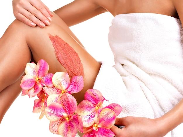 La ragazza con un bel corpo con fiore usando uno scrub sulla gamba su un bianco