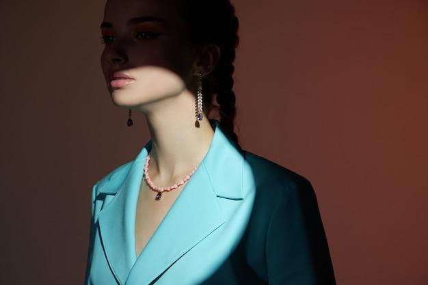 彼女の耳に美しいイヤリングを持つ少女、宝石を持つ女性の美しさの肖像画。完璧な滑らかな肌