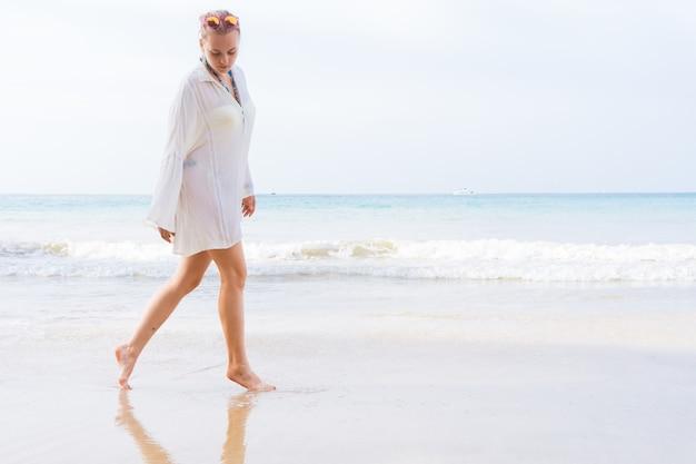 Девушка с красивыми ногами гуляет по пляжу