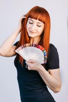 Девушка с красивым летним маникюром, держа образцы цветов ногтей. большой выбор цветов ногтей в профессиональной студии маникюра.
