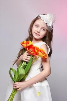 큰 파란색 애니메이션 눈을 가진 소녀와 그녀의 손에 튤립 꽃의 꽃다발. 세계 어머니의 날, 봄날, 아이의 손에 있는 봄 꽃다발. 긴 곱슬 금발 머리