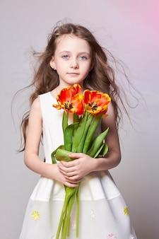 大きな青いアニメの目とチューリップの花の花束を手に持つ少女。世界の母の日、春の日、子供の手の中の春の花束