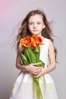 Girl with big blue anime eyes and a bouquet of tulip flowers in her hands. world mother's day, spring day, spring bouquet in the hands of the child. long curly blond hair