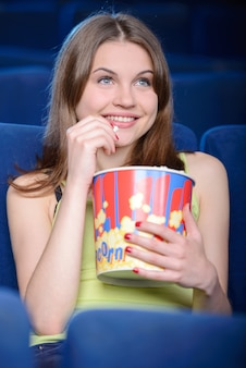 Girl with a big box of popcorn eats and watches a movie.