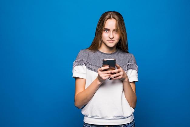 Ragazza con i grandi occhi facendo uso del nuovo telefono davanti alla parete blu