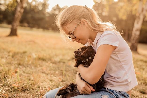 Девочка в больших очках смеется и играет с маленьким щенком