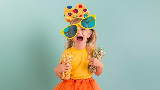彼女の手に大きなサングラスとキャンディーを持つ女の子