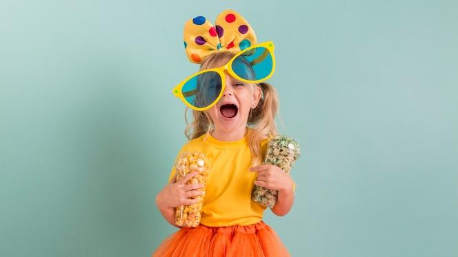Девушка с большими очками и конфетой в руках