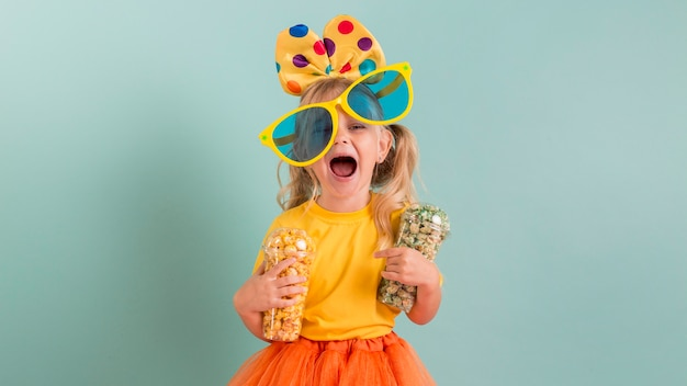 Ragazza con grandi occhiali da sole e caramelle nelle sue mani