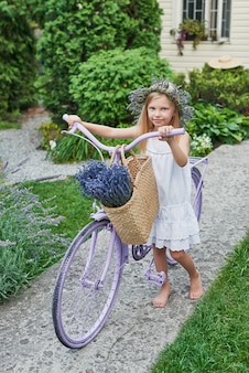 Girl with bike and lavender in summer in the yard