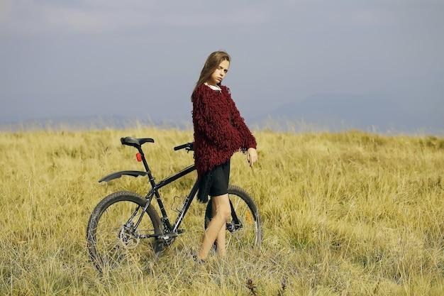 Girl with bike on mountain