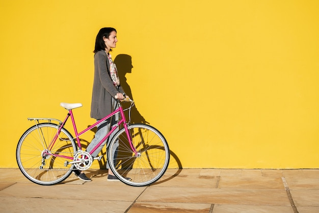 Girl with a bike walking in front of yellow wall