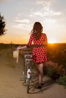 뒤에서 본 일몰 시골에서 걷는 자전거 소녀