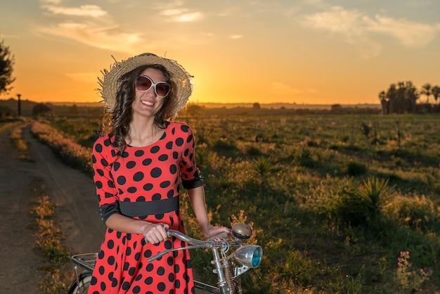 선글라스와 함께 웃 고 일몰에 시골에서 걷는 자전거 소녀