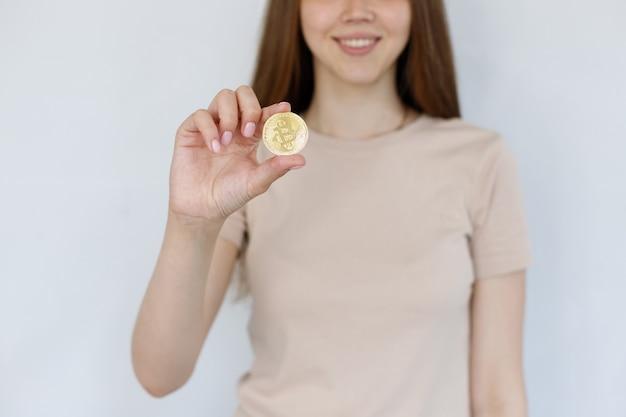 灰色の背景にビットコインのクローズアップを持つ少女