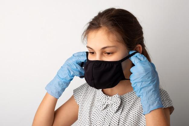 Девушка с черной одеждой, медицинской маской и перчатками в студии