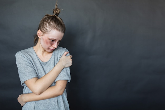 A girl with a black eye after a fight with her husband and boyfriend stands on a dark wall, hugs herself, is sad. domestic violence. aggression of the husband.