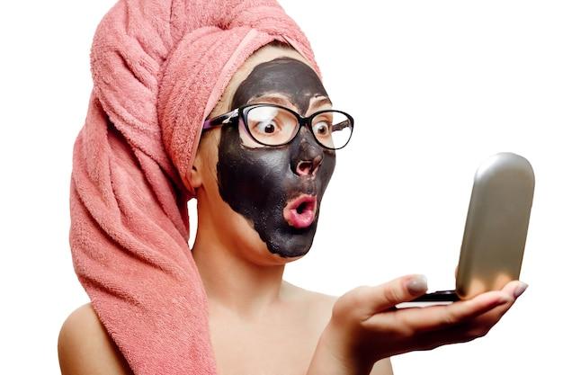 白い背景に黒いフェイスマスク、クローズアップの肖像画、彼女の頭に孤立した、ピンクのタオル、眼鏡をかけているビジネスウーマン、女の子は小さな鏡で自分自身に驚きを持って見えます、
