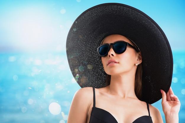 ビーチで黒い帽子とサングラスをかけた女の子