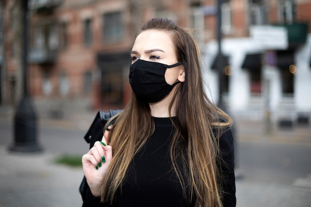Girl with a black mask on her face walks around the city
