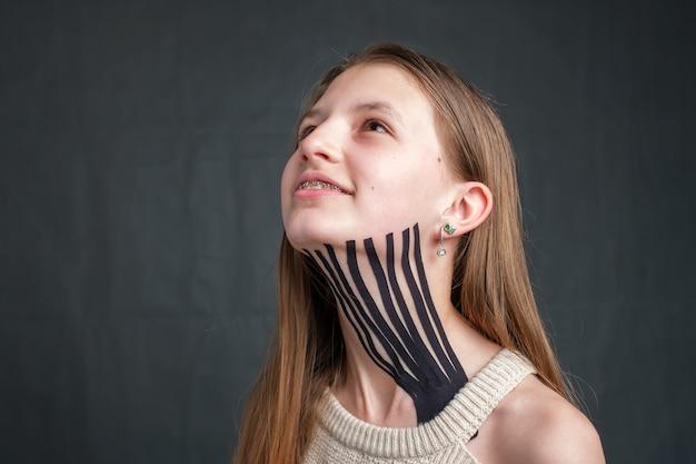 검은 줄무늬 운동 요법 테이프를 가진 소녀는 목에 배치