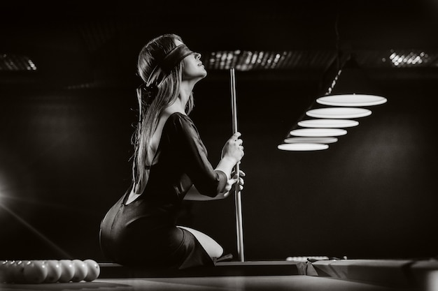 A girl with a blindfold and a cue in her hands is sitting on a table in a billiard club.russian billiards. black and white photo.