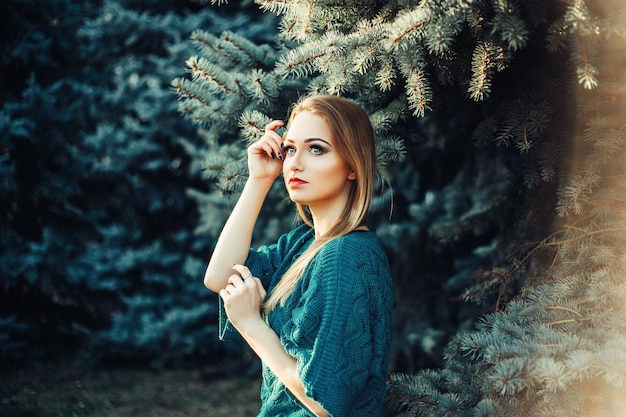 A girl with blond hair and blue eyes in a green sweater in a park near the green blue fir tree