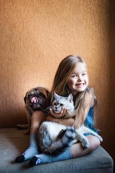ブロンドの髪を持つ少女は猫を保持します