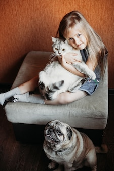 Girl with blond hair holds a cat