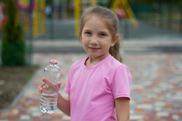 금발의 긴 머리를 가진 소녀는 공원의 건강한 생활 방식 개념에서 놀이터에 물병을 들고 있습니다