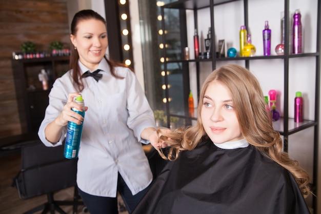 미용사에 의해 금발 물결 모양의 머리를 가진 소녀입니다. 헤어스프레이와 여성 클라이언트가 있는 헤어스타일리스트. 미용 미용실에서 젊은 여자. 헤어스타일.