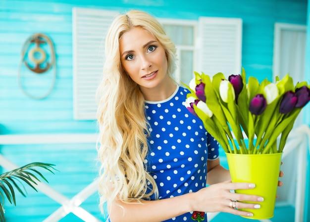 ブロンドの髪と目を閉じた女の子は彼女の手に白と紫のチューリップと花瓶を保持します